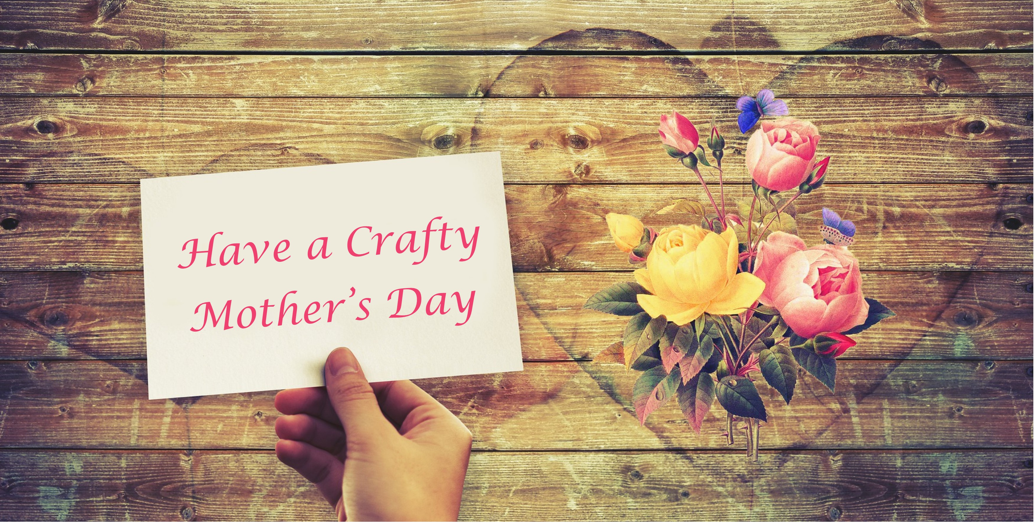 Hand holding a card with the wording Have a Crafty Mother's Day in pink writing, above a wooden background with a rose bouquet in a heart shape to the right